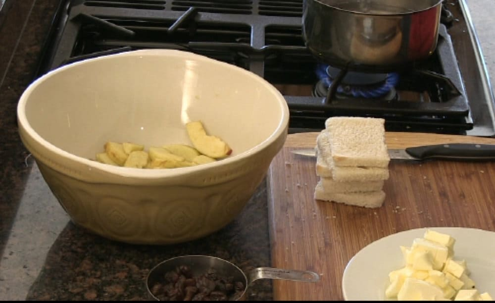 A bowl filled with apples coated in spiced flour next to a cutting board with sliced bread on it.