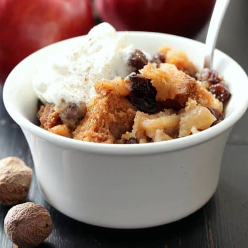 A white bowl with apple brown better with a silver spoon in next to whole nutmegs.