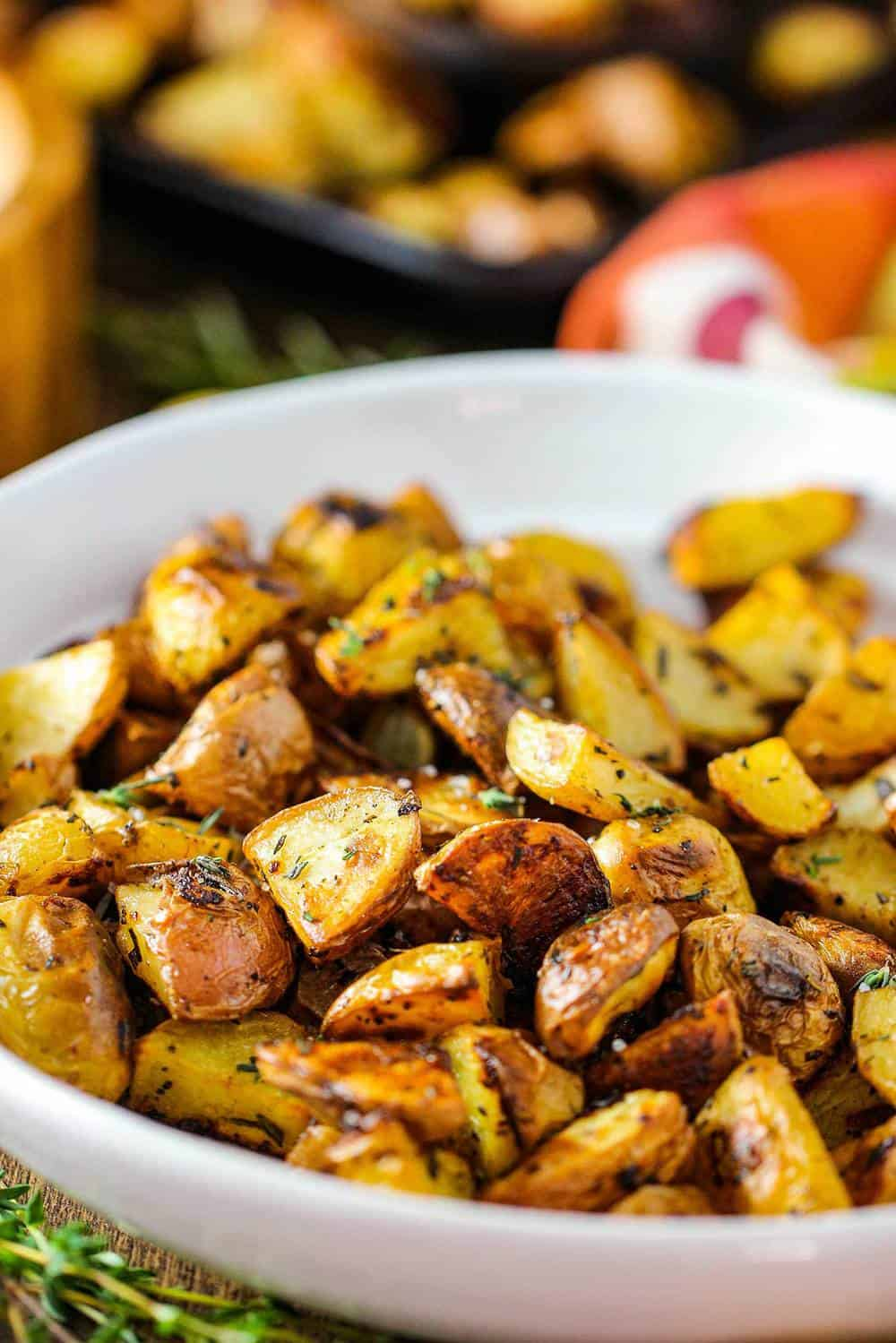 Roasted potatoes with balsamic and herbs in a white bowl.