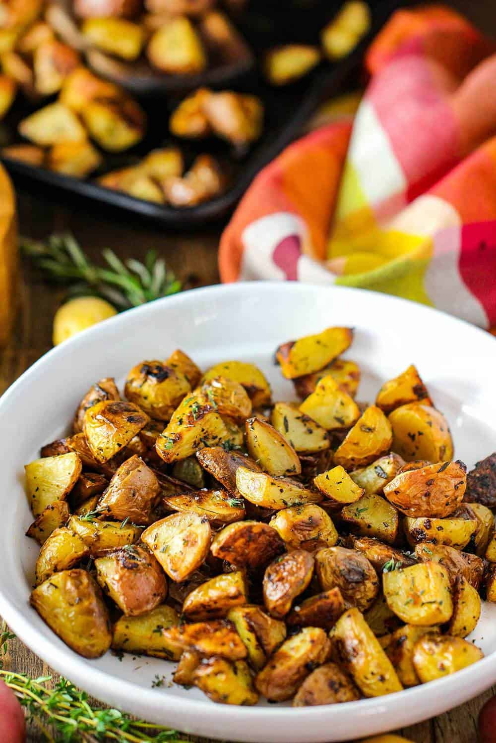 Roasted potatoes with balsamic and herbs in a white bowl with a colorful napkin next to it.
