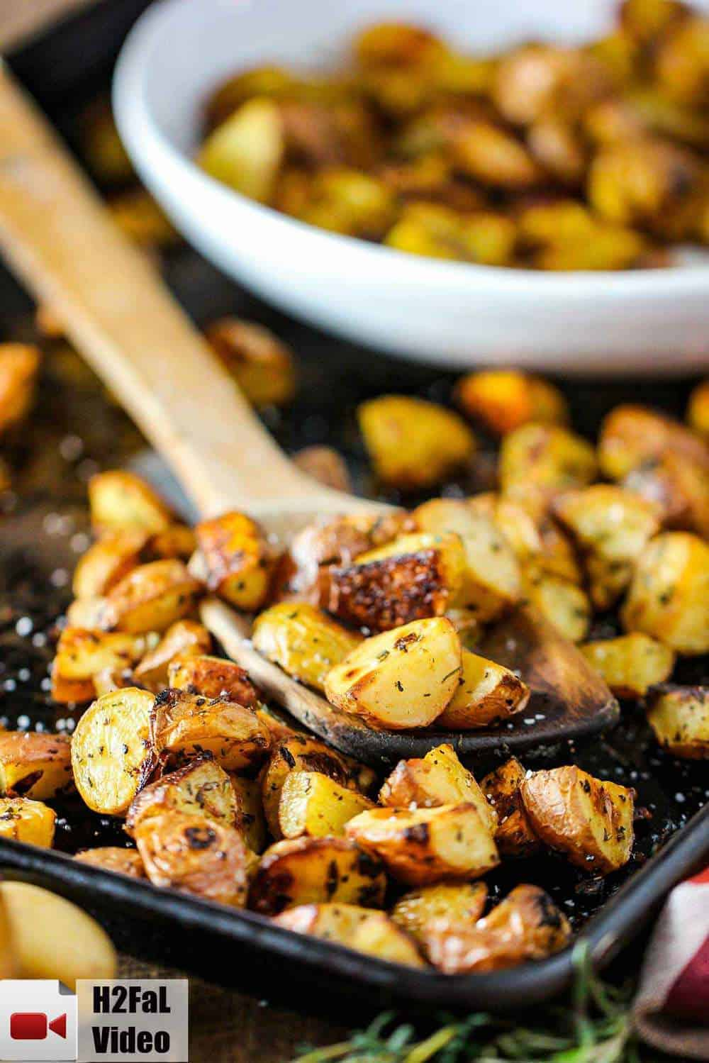 Roasted potatoes with balsamic and herbs on a baking sheet with a wooden spoon.