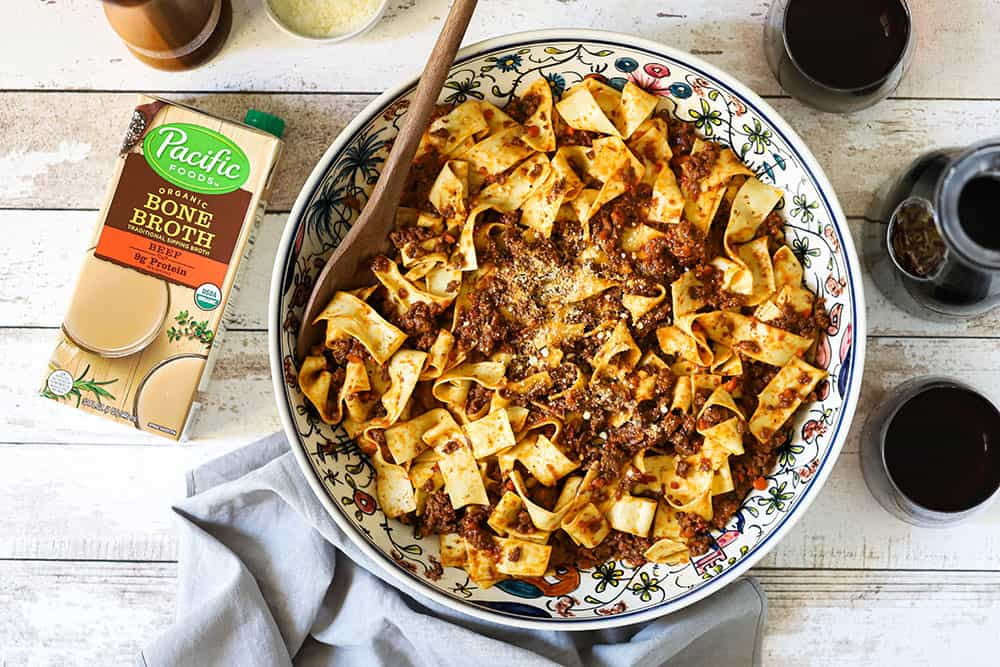 A large Italian pasta bowl filled with Pappardelle Bolognese sauce sitting next to a carafe and 2 glasses of red wine, and a box of Pacific Foods beef broth.