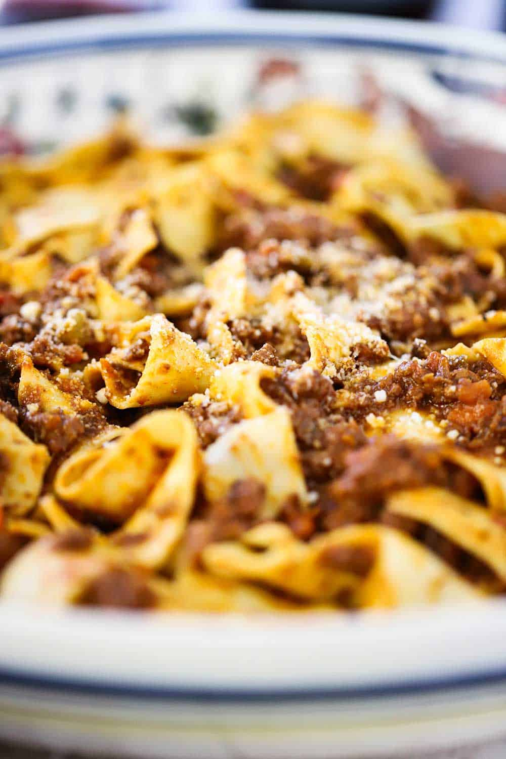 A close-up view of a large Italian pasta bowl filled with homemade pappardelle bolognese.