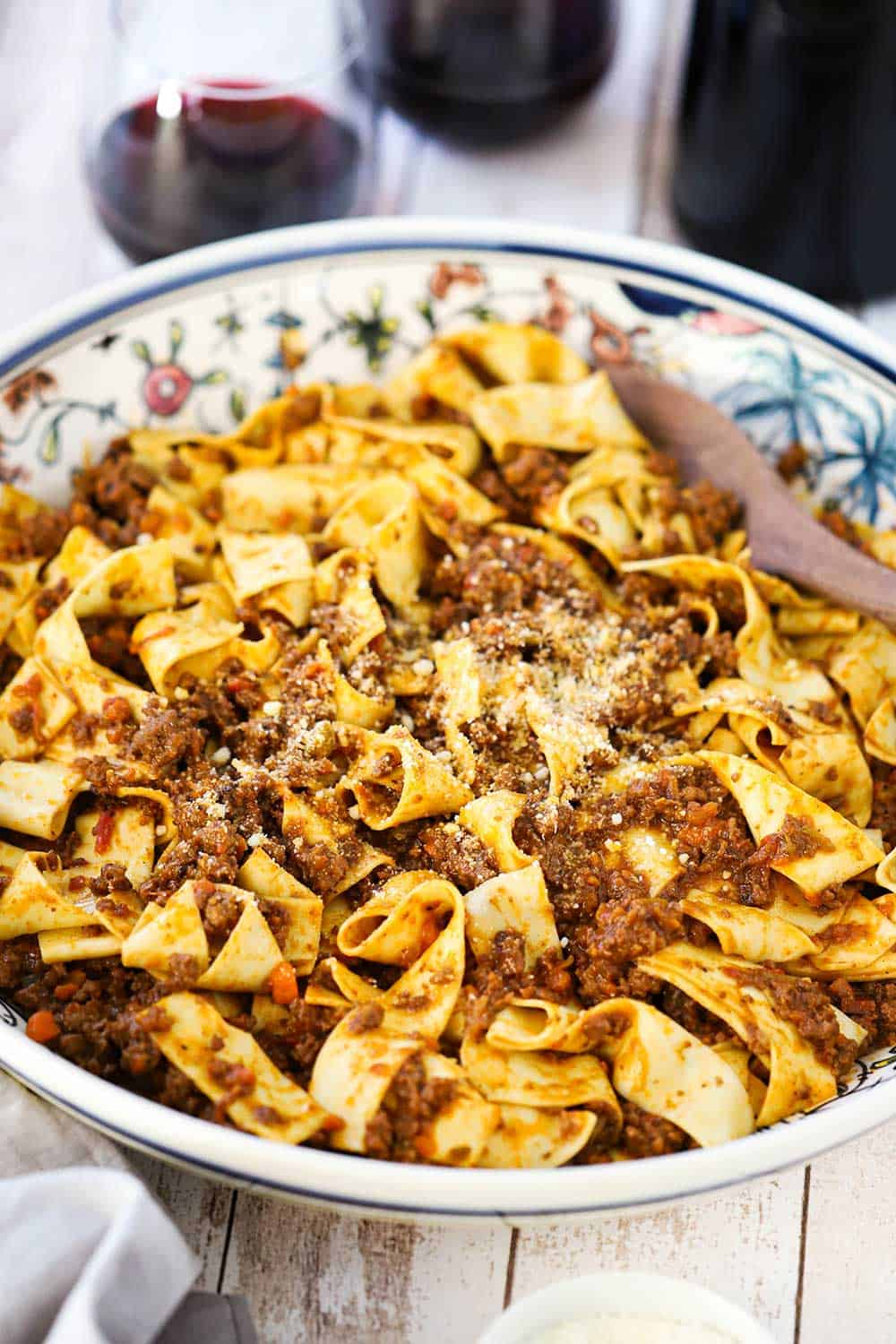 A view looking downward into an Italian pasta bowl filled with pappardelle bolognese pasta next to a couple stemless wine glasses filled with red wine.