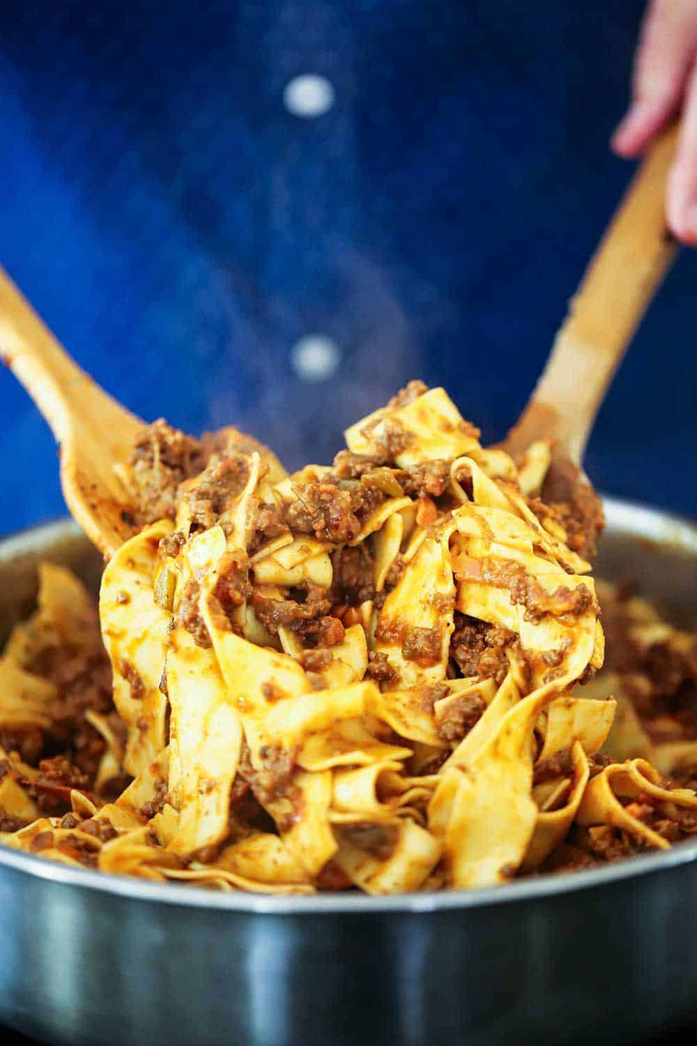 Two hands holding two wooden spoons tossing pappardelle bolognese in a large silver skillet.