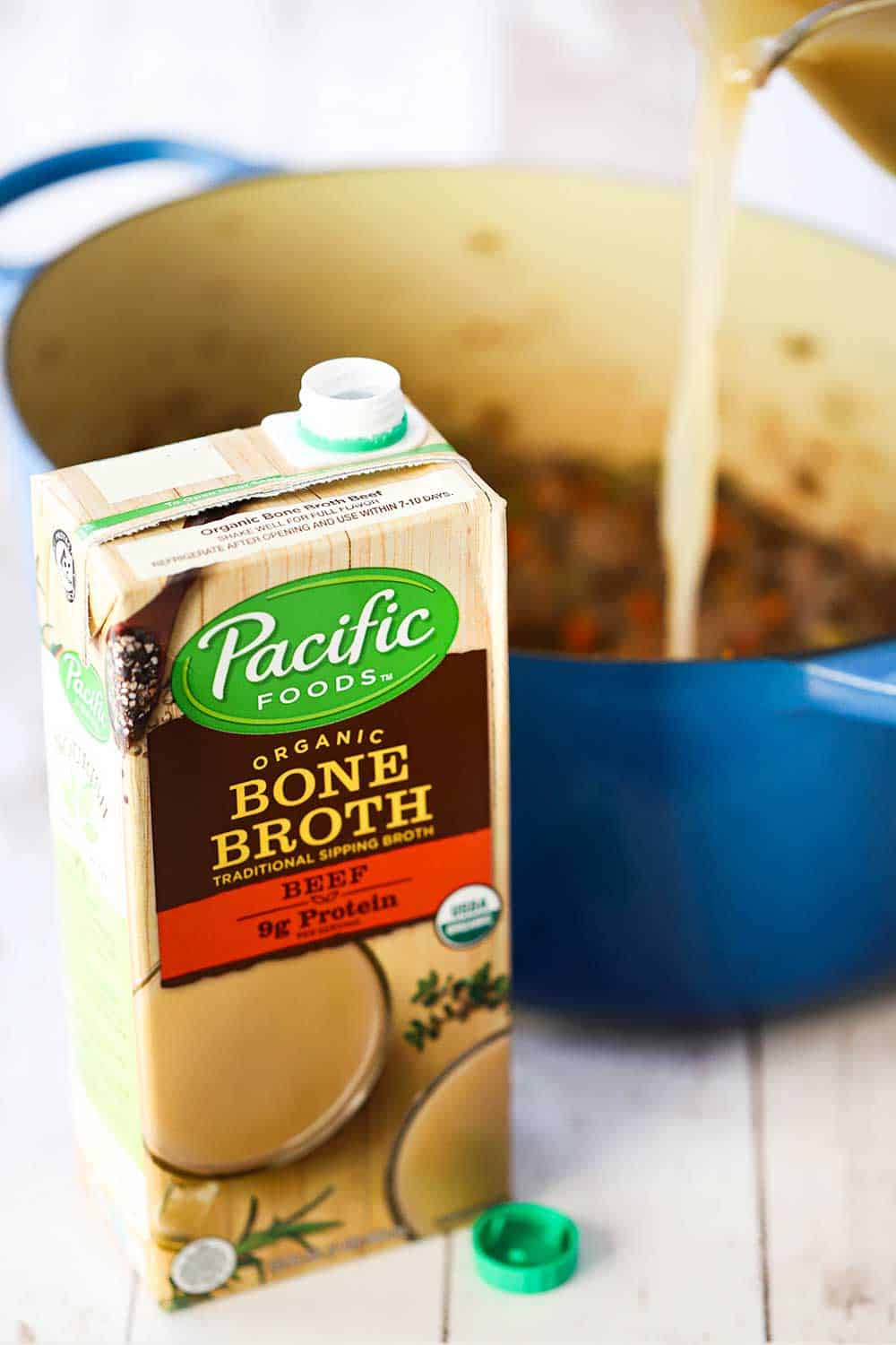 A box of Pacific Food bone broth sitting in front of a blue Dutch oven with a measuring cup pouring the broth into the pot.