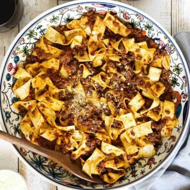 A large patterned Italian pasta bowl filled with Pappardelle Bolognese and a small bowl of Parmesan cheese next to it.