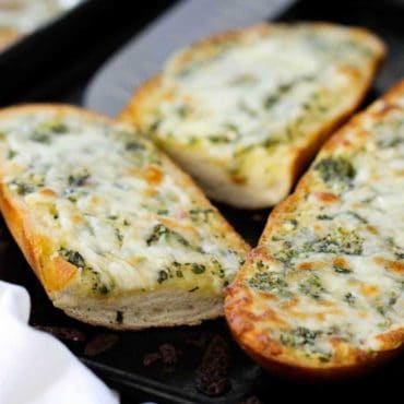 Sliced cheesy garlic bread on a baking sheet.