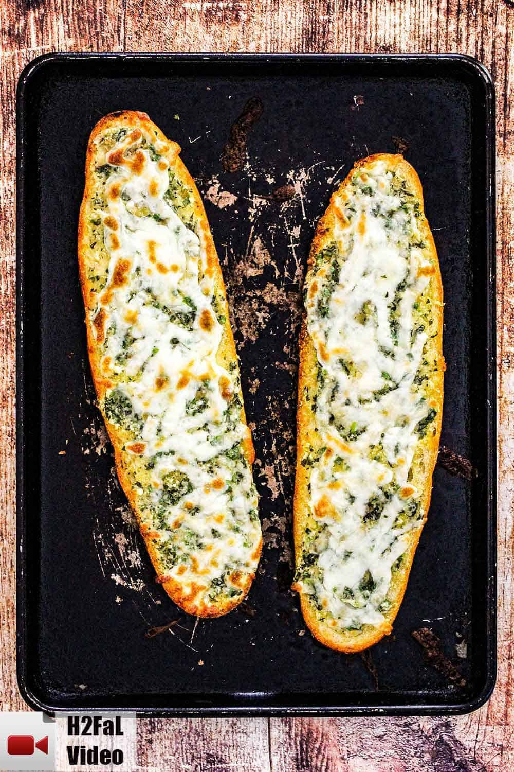 Two loaves of cheesy garlic bread on a scratched black baking pan.