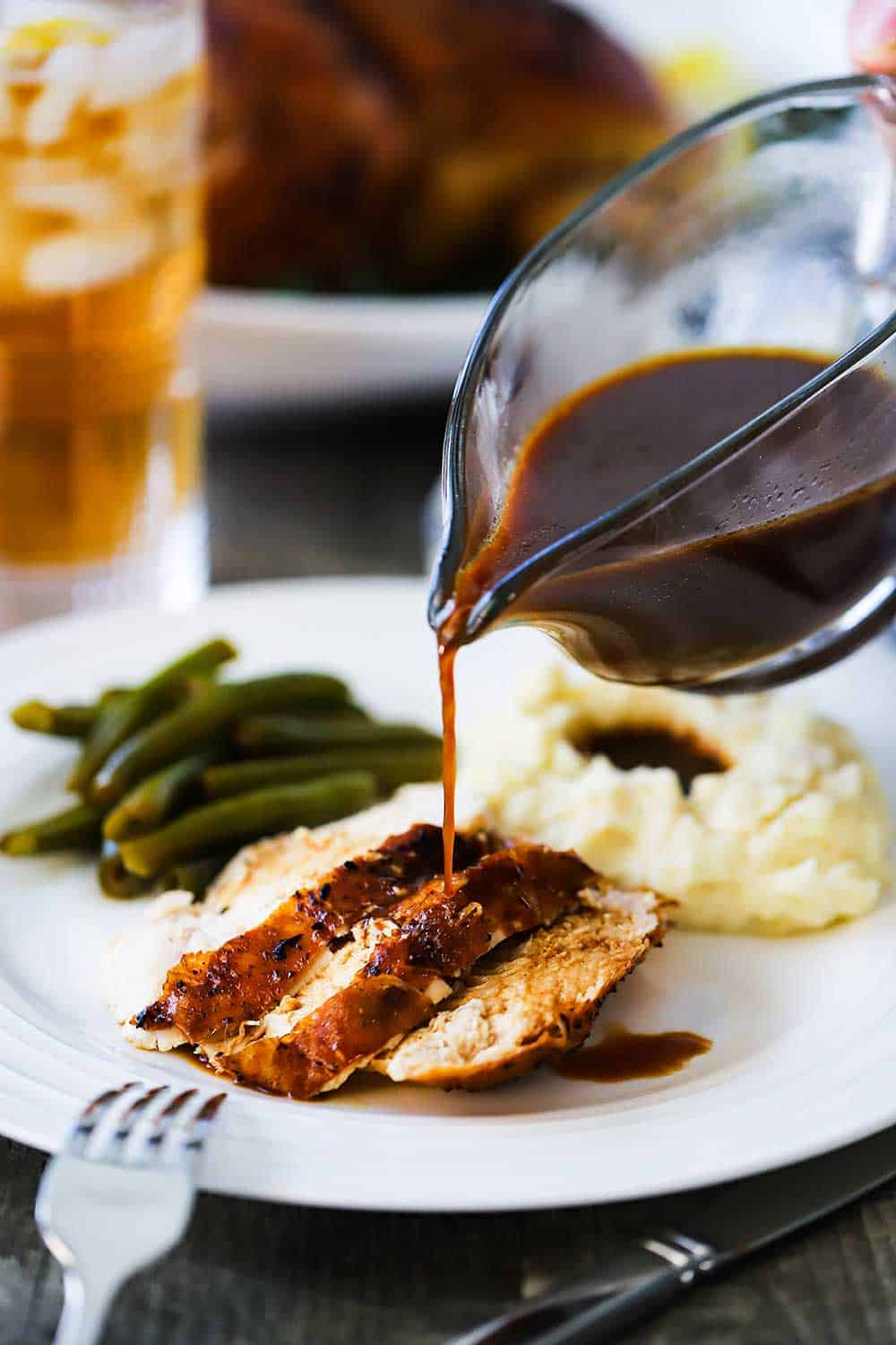 Brown gravy being poured from a glass gravy boat over sliced roasted chicken next to mashed potatoes and green beans.