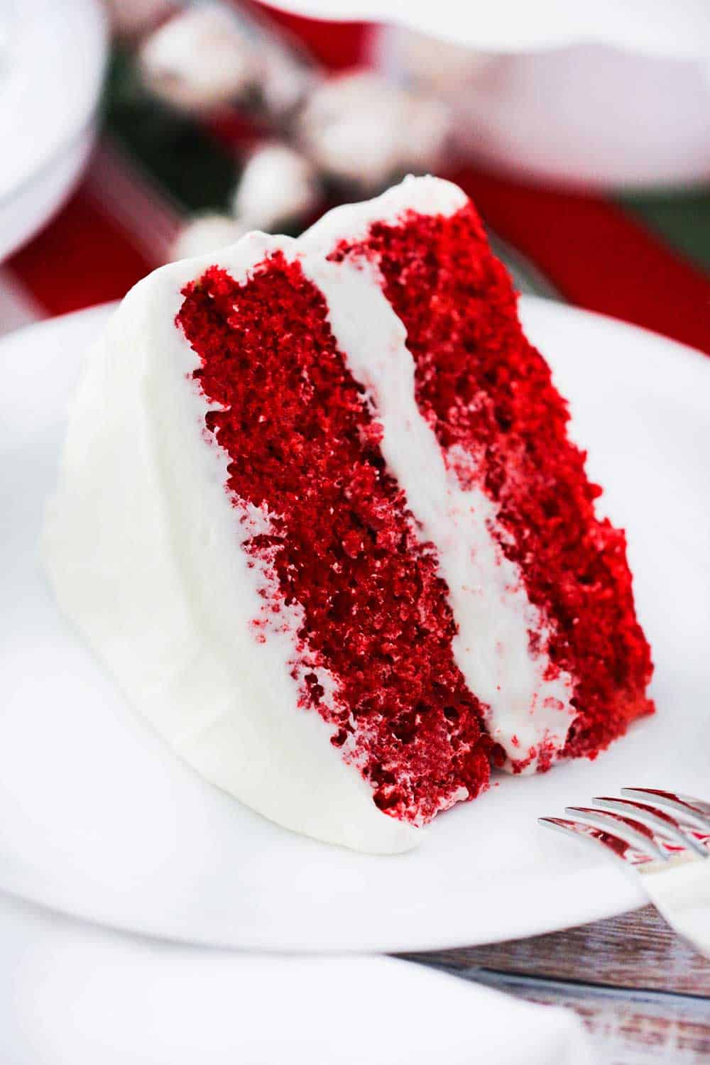 A large slice of red velvet cake on a white plate.