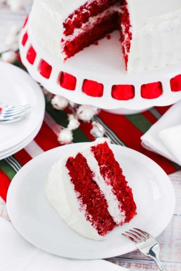 A slice of red velvet cake on a white plate next to the cake on a cake stand with red ribbon.