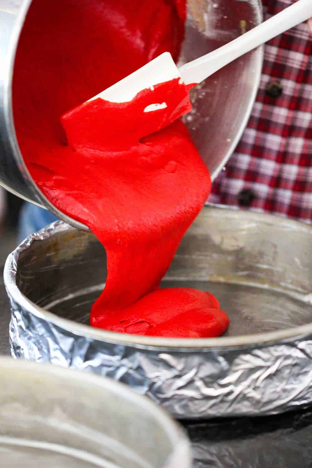 Red cake batter being poured into a cake pan lined with foil.