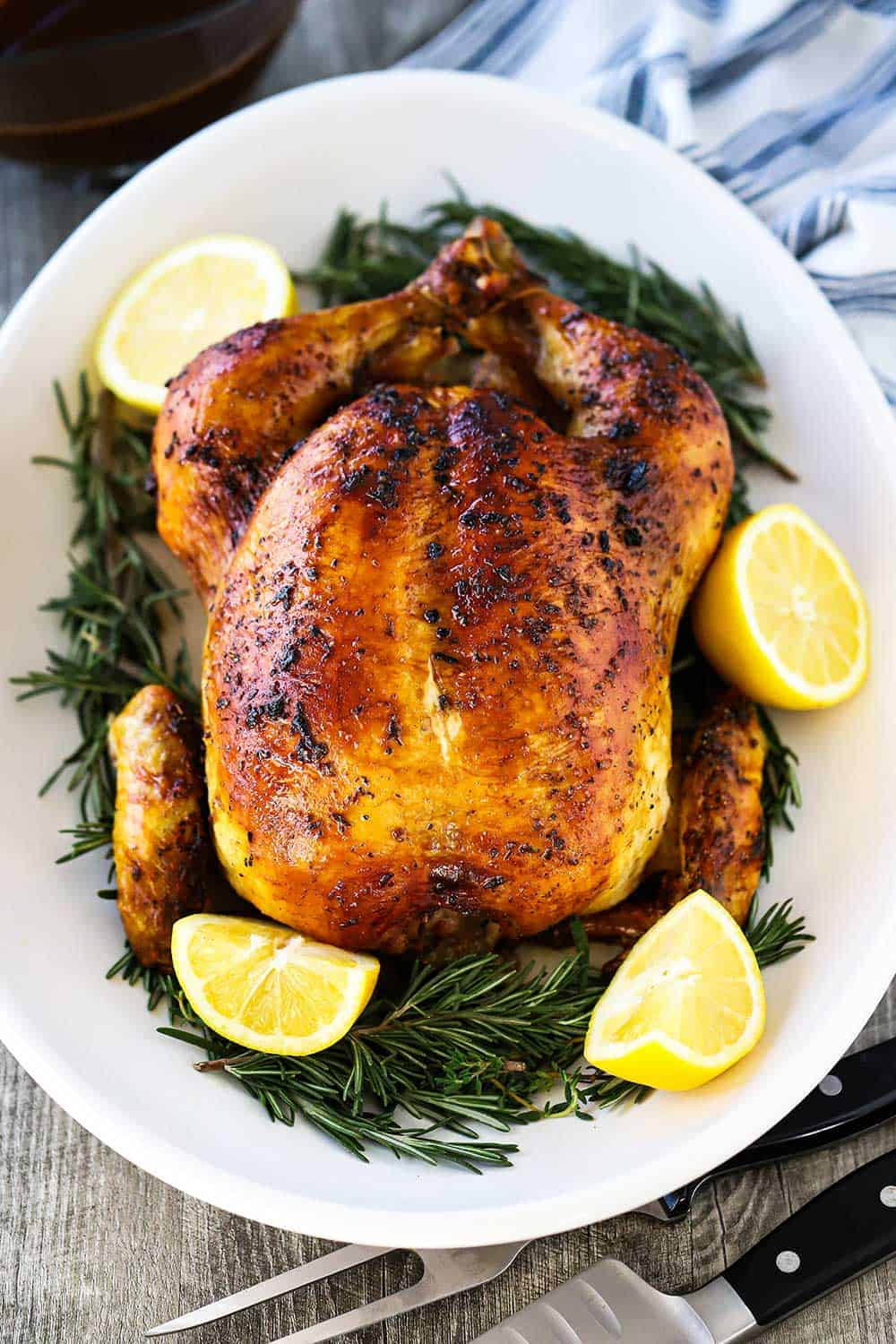 A roast chicken sitting on an oval platter with sliced lemons and herbs surrounding the bird.