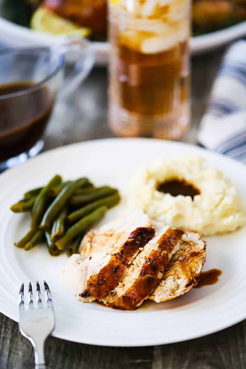A white dinner plate filled with sliced roasted chicken, mashed potatoes and gravy, and green beans.