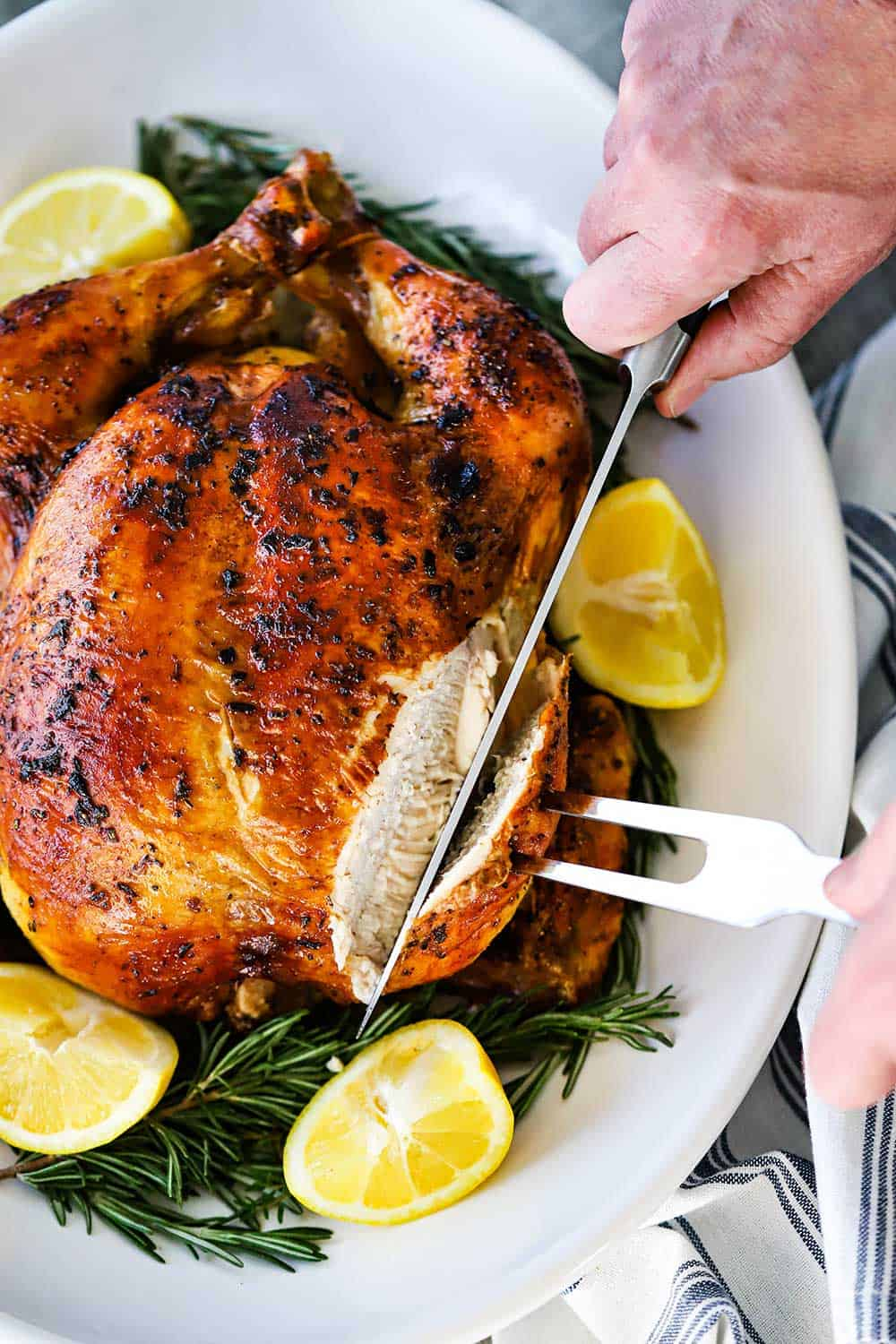 A person using a large fork and knife to slice in a roast chicken on a platter with cut lemons and herbs surrounding the bird.