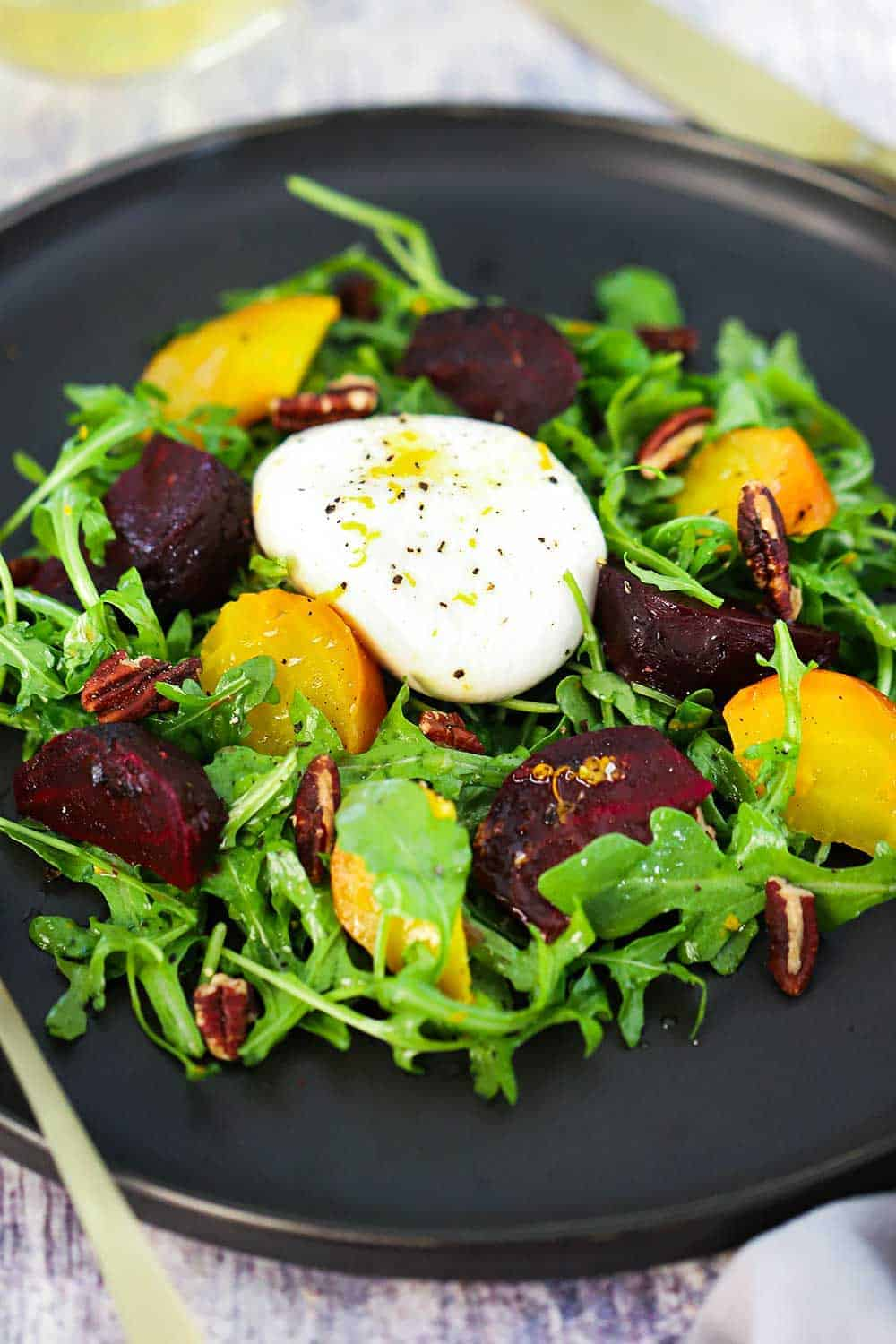A dark circular plate filled with roasted beet and burrata salad.