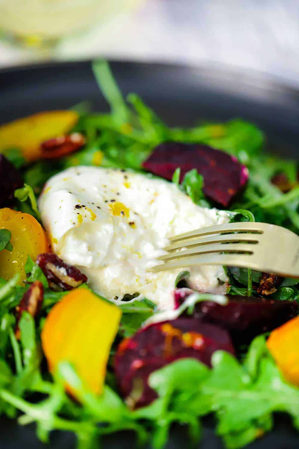 A fork breaking open a ball of burrata cheese sitting on top of sliced roasted beets and arugula salad.