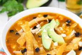 A white bowl filled with tortilla soup topped with avocado slices, tortilla strips, and a lime wedge all sitting next to a glass of beer.