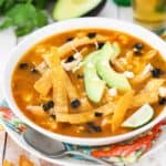 A bowl of chicken tortilla soup in a white bowl surround by a glass of beer and slice avocado.