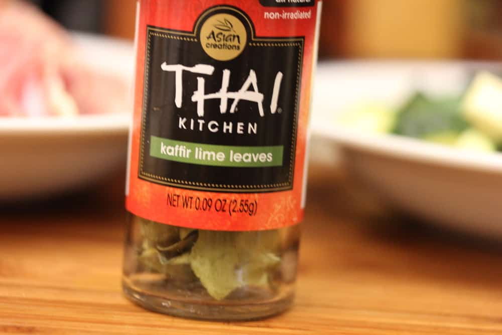 A bottle of Thai Kitchen kaffir lime leaves on a wooden cutting board.
