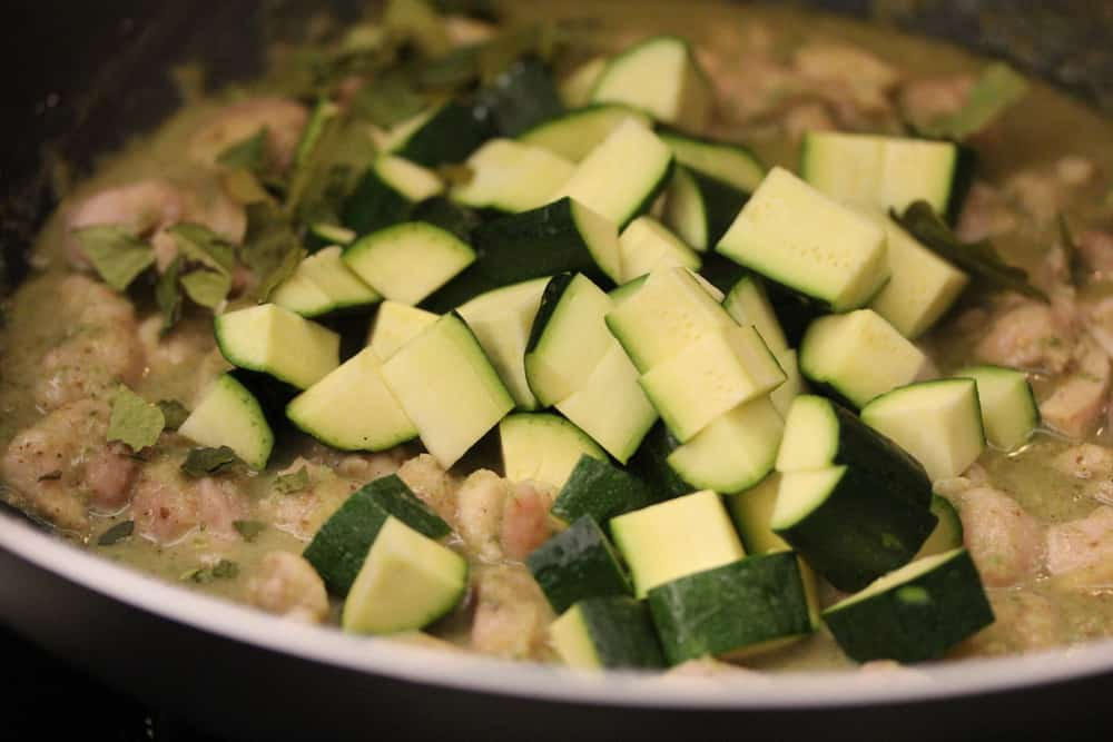 Chopped zucchini in a pot of cooked chicken and Thai ingredients all in a large skillet.