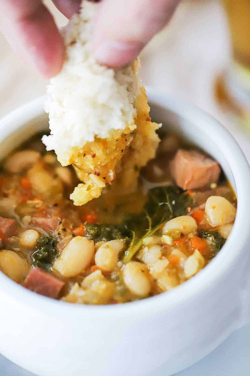 A hand dipping a torn piece of bread dipping into a bowl of smoked sausage and white bean stew.