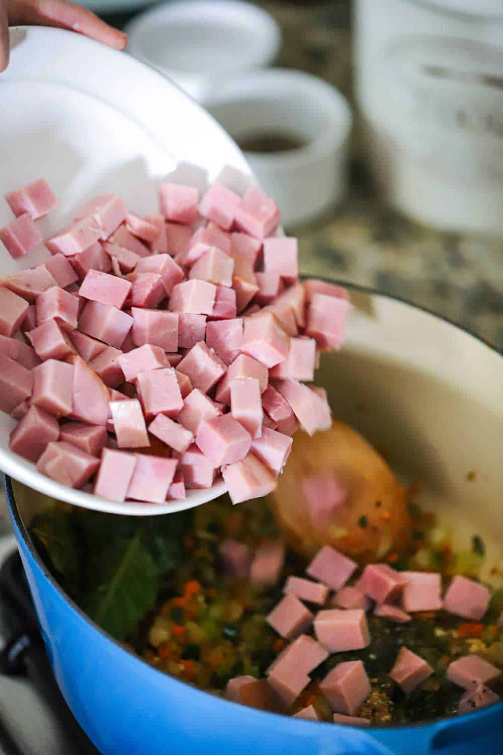 A bowl of cubed smoked ham being dropped into a Dutch oven filled with sautéed vegetables.