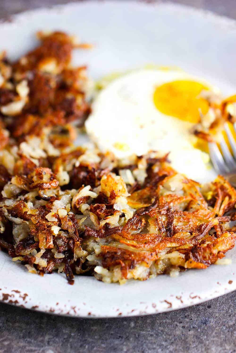 Perfectly cooked crispy hash browns on a plate with an egg