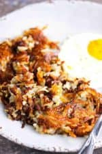 Crispy hash browns on a plate next to a fried egg