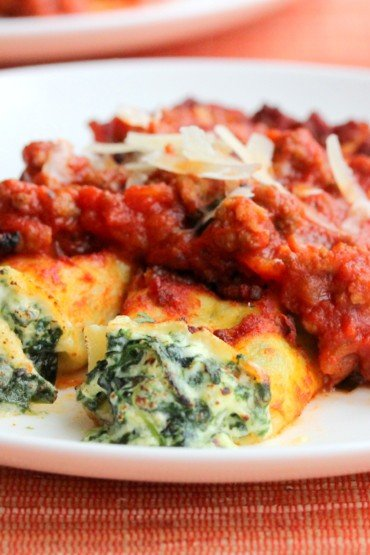 A white plate of cheese and spinach cannelloni