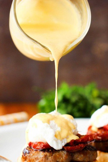 Easy hollandaise sauce being poured onto eggs Benedict