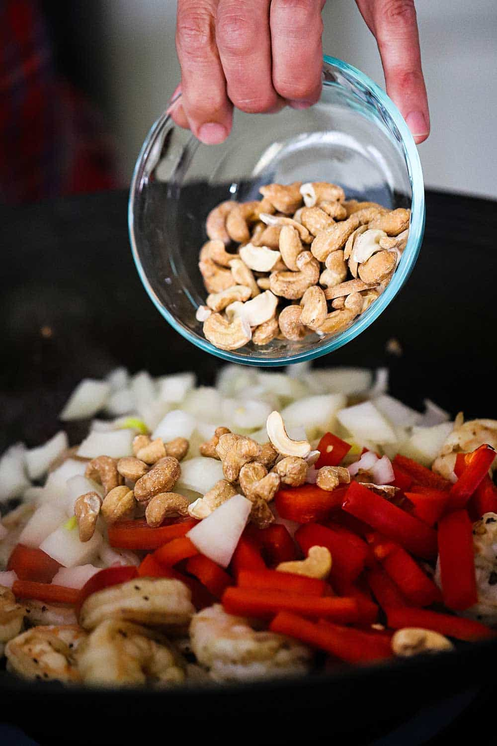 A person dumping whole roasted cashews from a small glass bowl into a wok filled with cooked shrimp and chopped onion and red bell pepper.