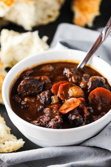A white bowl filled with hearty beef stew next to torn white bread.