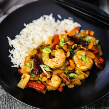 A black individual dinner plate with cooked Jasmine rice on one side and a serving of Kung Pao Shrimp on the other side.