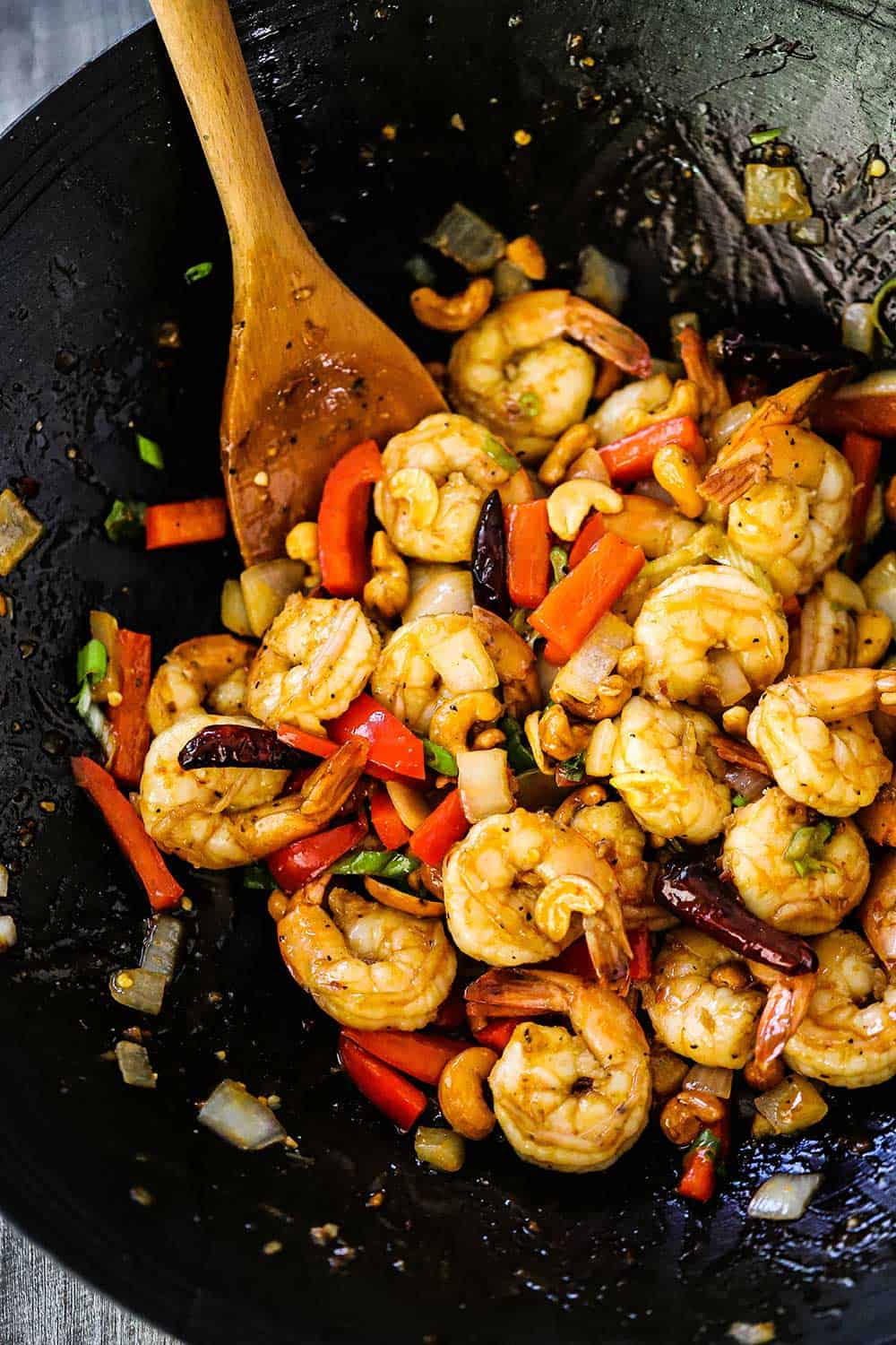 A wok filled with fully cooked Kung Pao Shrimp and a wooden spoon inserted in the middle of it all.
