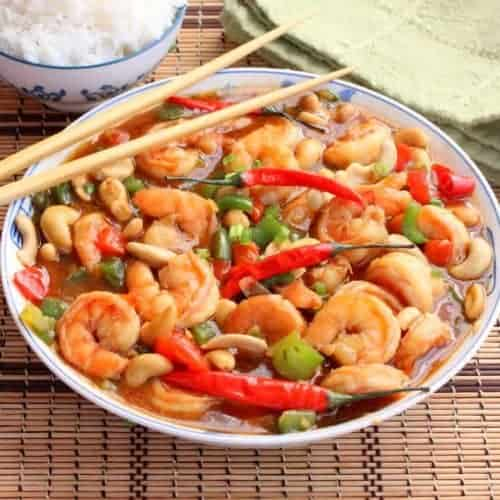 A large Asian bowl filled with Shrimp Kung Pao with chop sticks sitting on top, next to a bowl of steamed white rice, all on a wicker mat.