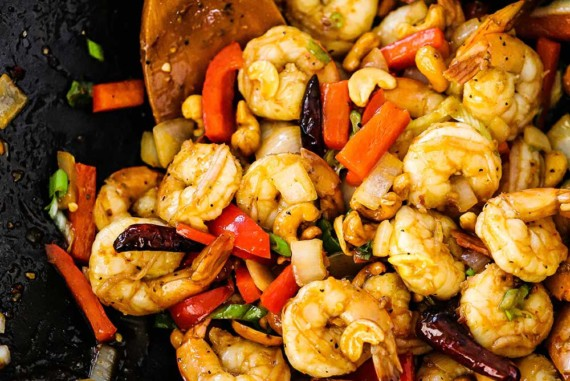 A wok filled with cooked Kung Pao Shrimp with a wooden spoon inserted into the mixture.