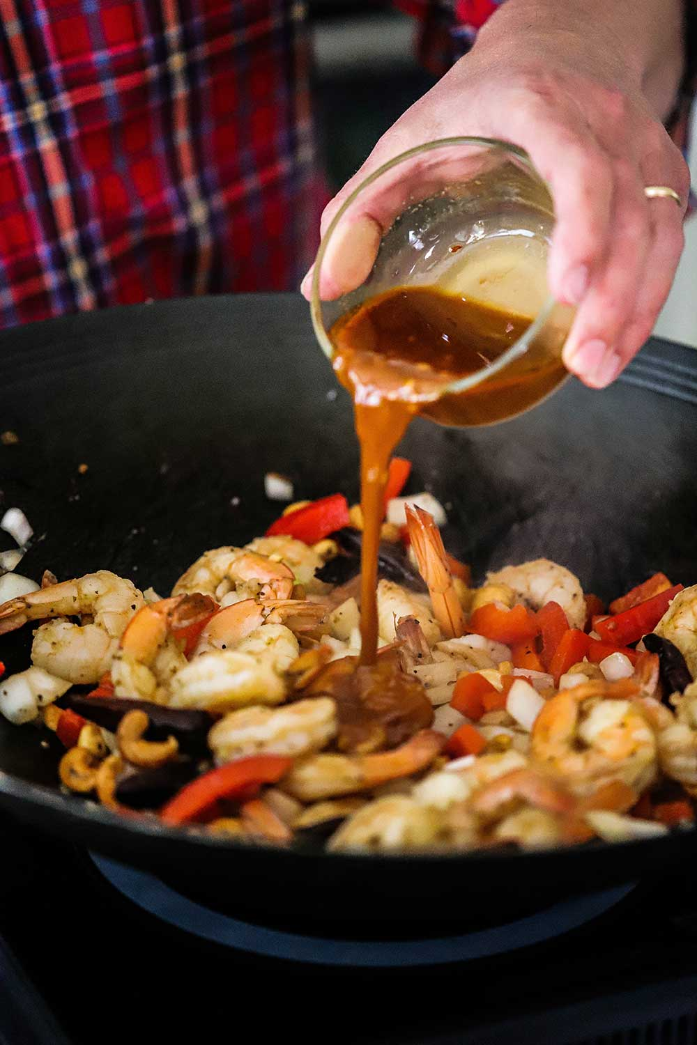A person pouring kung pao sauce from a small glass bowl into a wok filled with sautéd shrimp, onions, red bell peppers, garlic, and dried chilies.