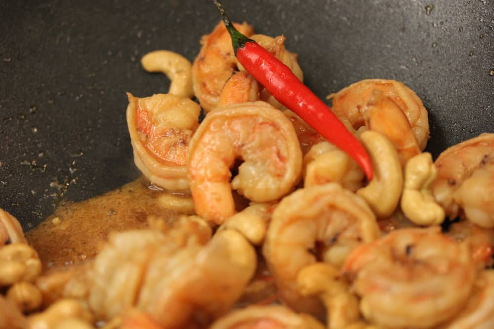 Shrimp and hot red peppers cooking to a nice pink color in a large black wok.