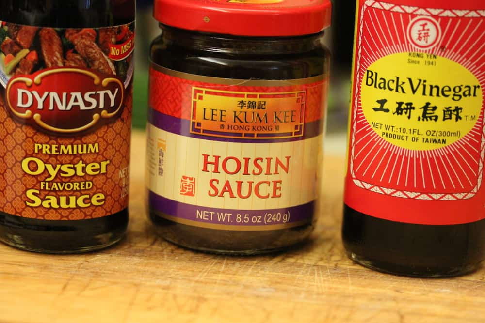 A shot of a bottle of oyster sauce, a bottle of Hoisin sauce, and a bottle of Chinese black vinegar.