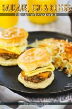 Two sausage, egg, and cheese breakfast sandwiches on a dark plate with hashbrowns in front a glass of orange juice.