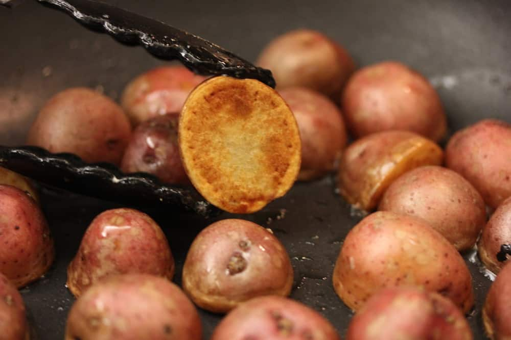 A pair of tongs holding a red potato in a skillet