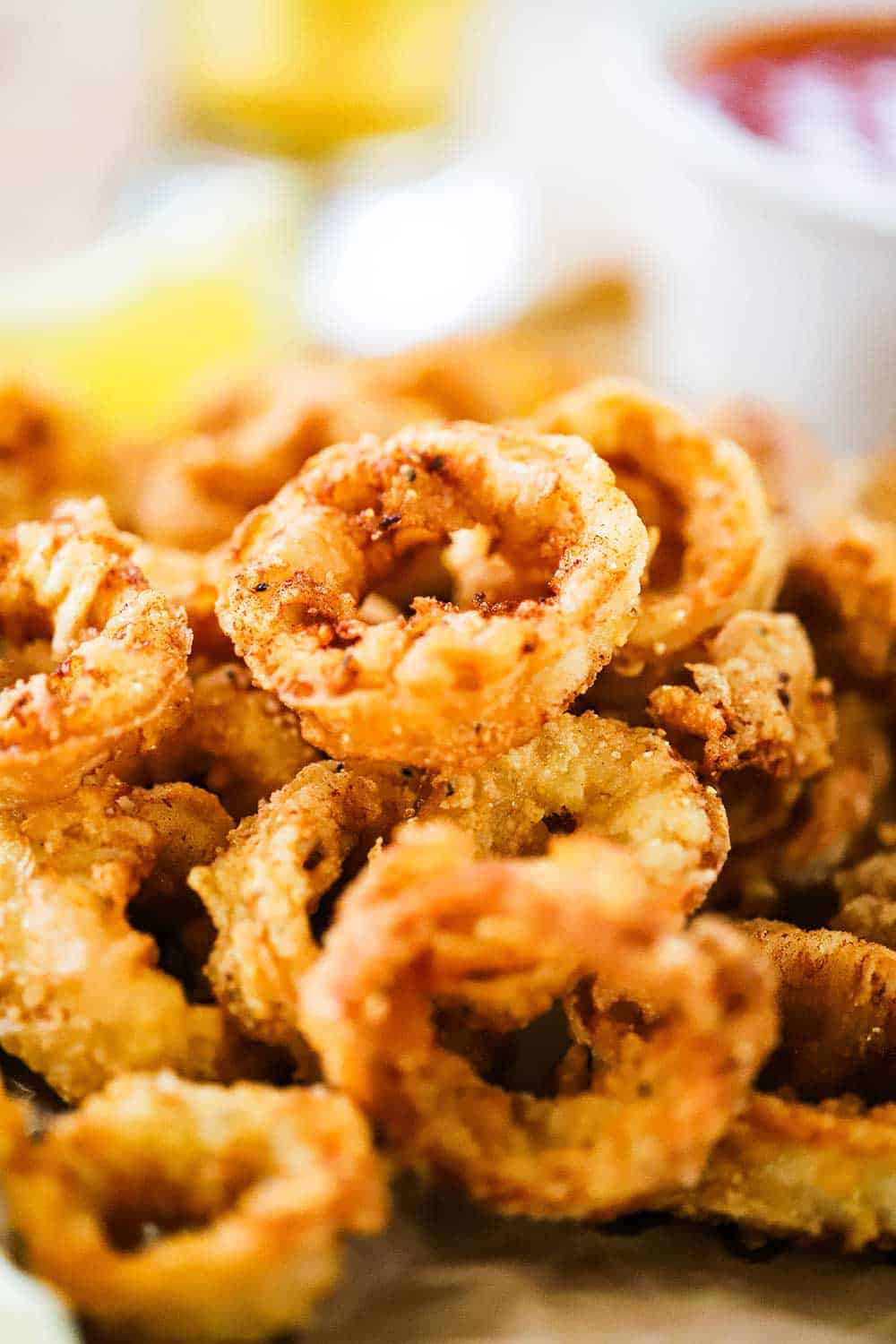 A pile of fried calamari sitting next to a small white bowl filled with marinara sauce.