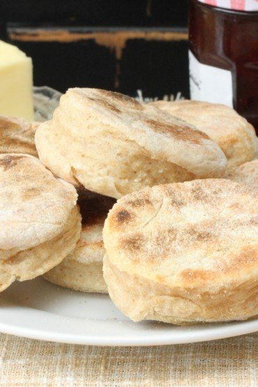 A plate full of homemade English muffins next to stick of butter.