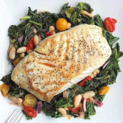 Halibut with braised kale, beans & tomatoes on a white plate