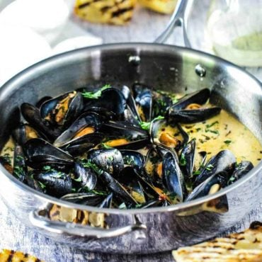 mussels with garlic and wine in a large silver saucepan.