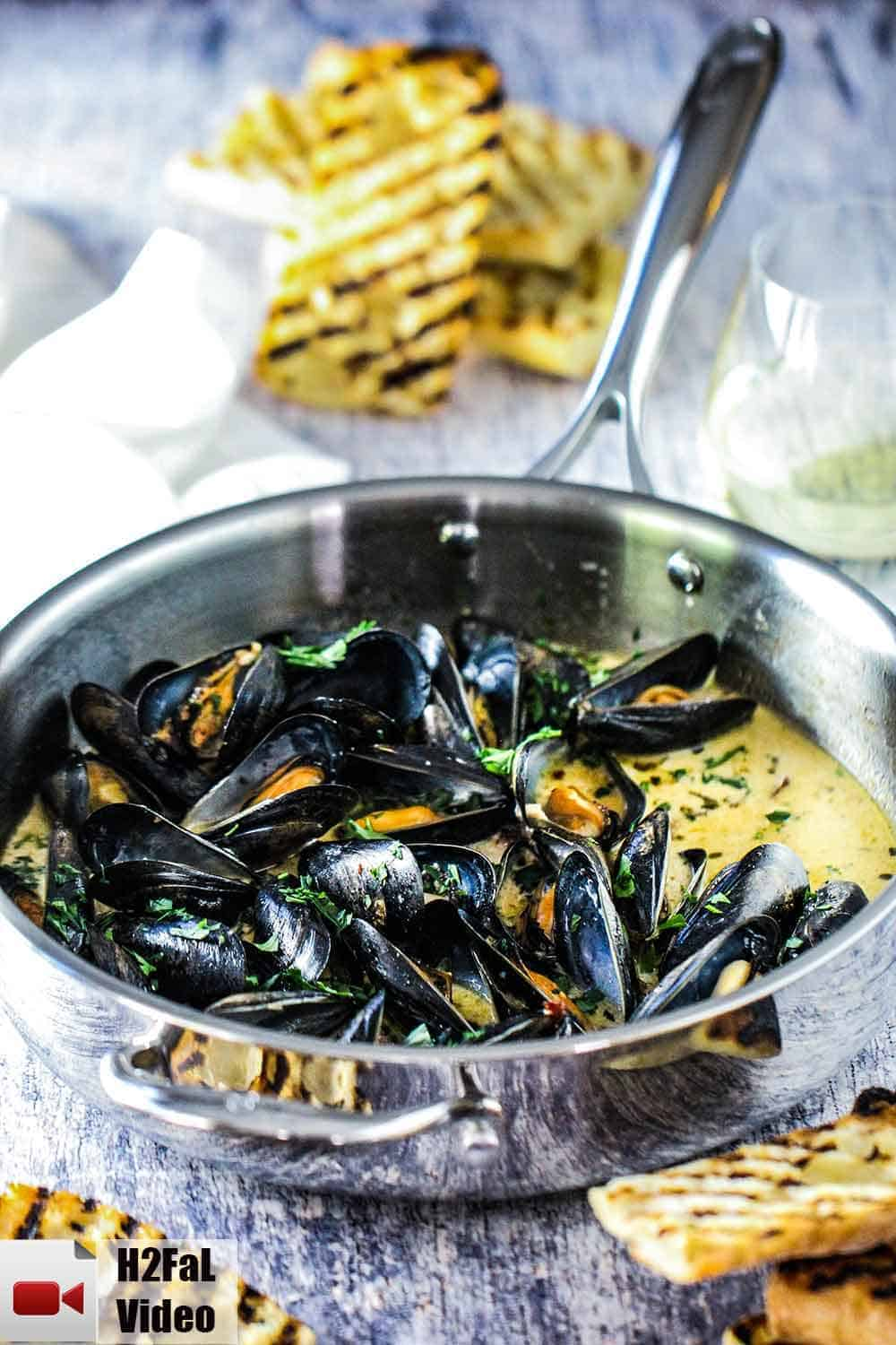 A large silver sauce pan with mussels and garlic and wine in it