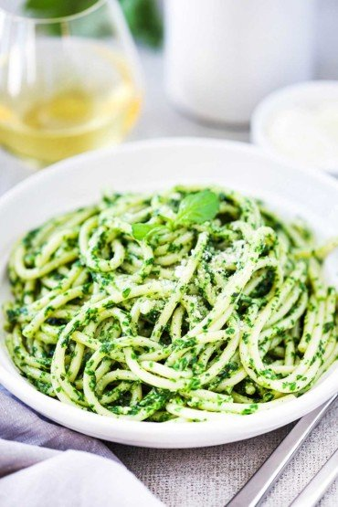A white bowl filled with pesto pasta next to a grey napkin, two forks, and glass of white wine.