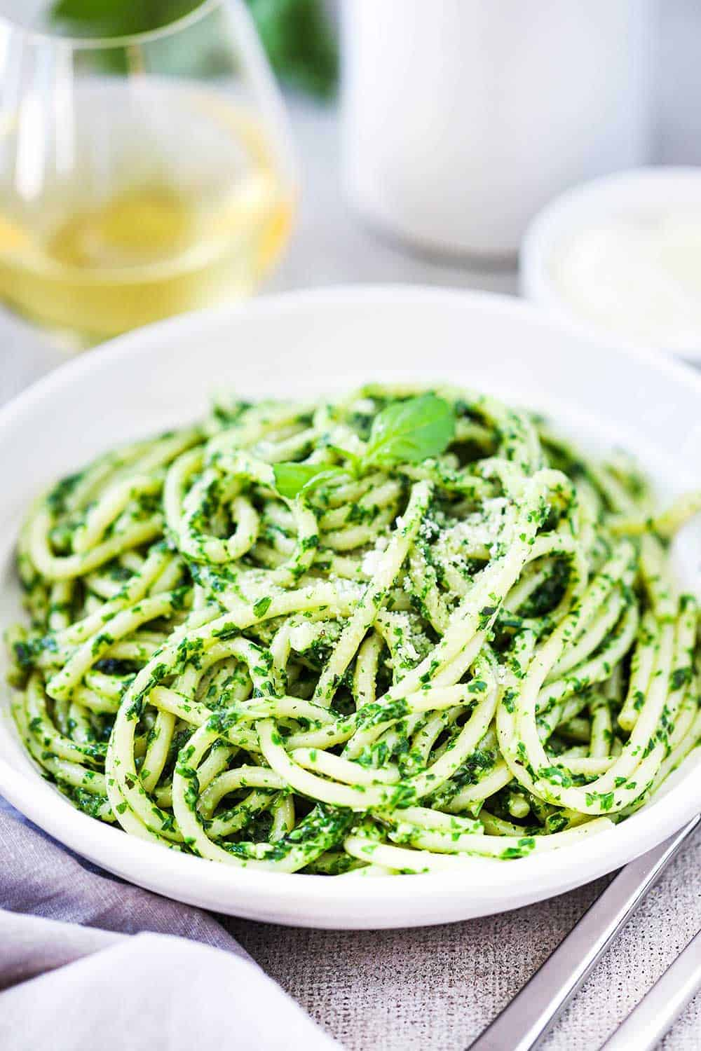 Pesto spaghetti served in a large white pasta bowl with shredded parmesan on top.